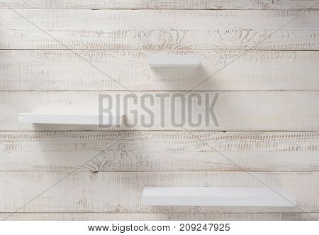 set of wooden shelves at white plank background texture