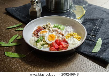 Healthy Hearty Cobb Salad with Chicken Bacon Tomato Onions Eggs green beans. American food. Close up home made cuisine