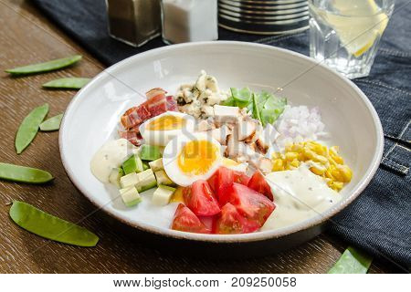 Healthy Hearty Cobb Salad with Chicken Bacon Tomato Onions and Eggs. American food. Close up home made