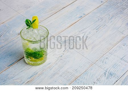 Alcohol mojito cocktil bar long drink fresh tropical beverage top view copy space highball glass, with rum, spearmint, lime juice, soda water and ice on white concrete table .