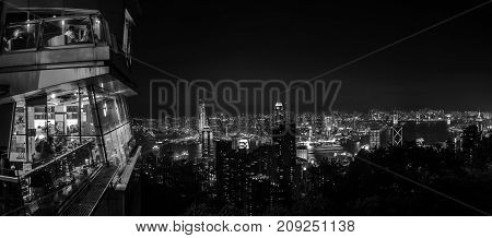 Hong Kong. Skyline of Hong Kong at night. Illuminated skyscrapers with restaurant on top of the mountain. Black and white