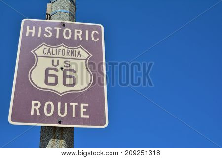 Historic California Route 66 road sign on a blue sky.