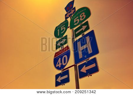 Interstate 40 road signs with dawn lights on San Bernardino county California.