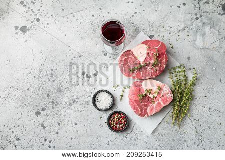 Fresh veal shank slices beef meat for Osso Buco cooking on cutting board with ingredients and seasonings thyme, pepper, salt.
