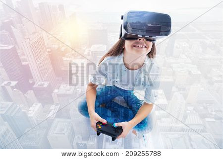 Keen on gaming. Adorable little girl in a VR headset sitting cross-legged and holding a video game controller while looking up and seating as if above the city