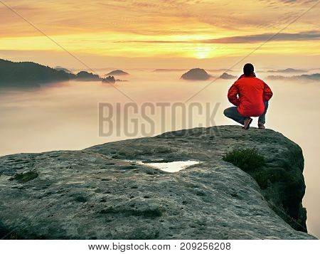 Man Hiker  At Mountain Peak. Marvelous Daybreak In Autumn Misty Landscape. Sun Hidden In Clouds