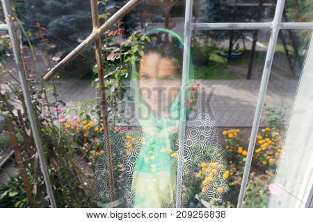 Reflection of a girl in a scarf in a window