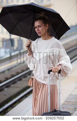 blond woman waiting at train station with suitcase and holding umbrella