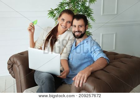 Young couple with laptop and credit card at home. Internet shopping concept