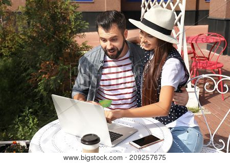 Young couple with laptop and credit card in open air cafe. Internet shopping concept
