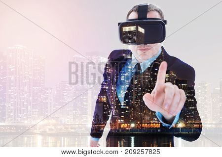 Futuristic device. Handsome bristled man in a business suit pointing with his finger at the camera and wearing a VR headset while his image being superimposed on the night city