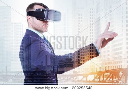 Testing quality. Good-looking young man in a business suit standing half-turned and raising his index finger while trying out his new VR headset
