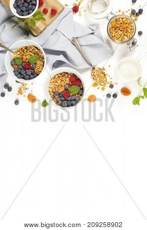 Homemade granola (with dried fruit and nuts) and healthy breakfast ingredients - honey, milk and berries on white background