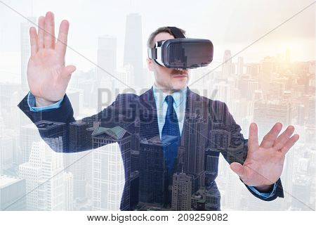 Gripping experience. Pleasant bristled young man wearing VR headset and raising his hands as if trying to stop something in the virtual reality while standing against urban background
