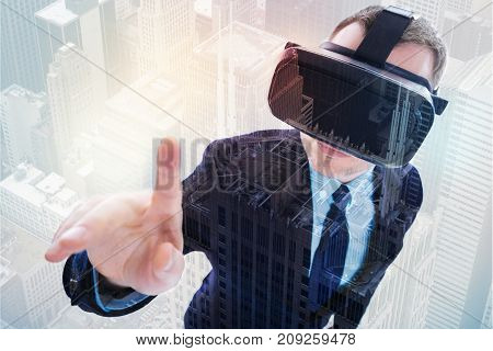Enjoying VR experience. Top view of a young neat businessman in VR headset raising his index finger as if being ready to touch the camera while standing against urban background