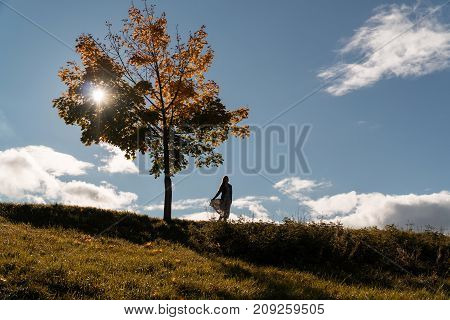 The Girl Is Standing On A Hill Beside A Lonely Tree