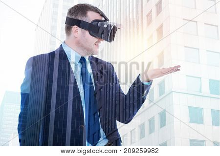 Maximum experience. Pleasant cheerful man in a business suit wearing a VR headset and holding an object on his palm in the virtual reality while being against an urban background