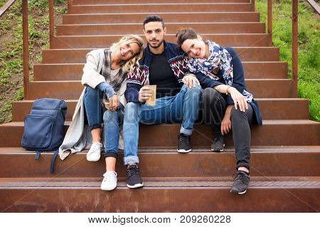 group of friends sitting outside on stairs and looking at camera