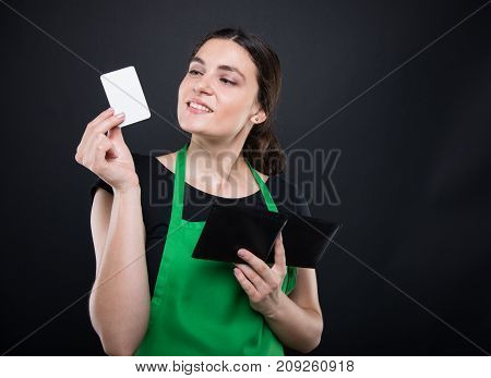 Smiling Female Clerk Holding Visit Card In Hand