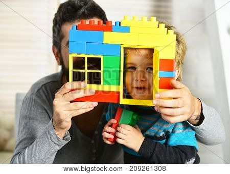 Dad and kid hide behind house wall made of plastic blocks. Boy and man on defocused background. Father and son with happy faces hold colorful toy bricks construction. Family game and childhood concept