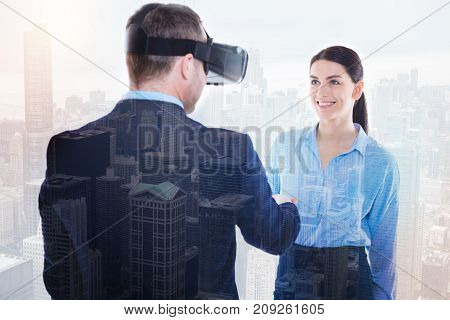 Firm handshake. Beautiful young woman giving her male colleague a handshake while the man wearing a VR headset