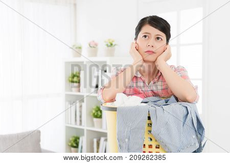 Woman Leaning On Laundry Basket Feeling Bored