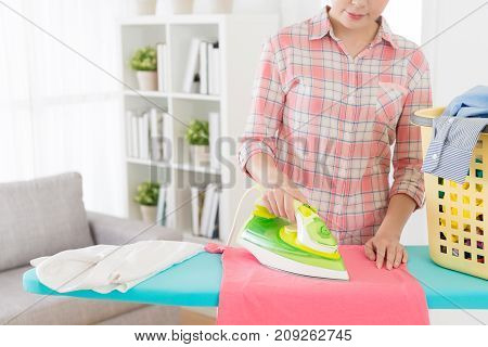 Housewife Ironing Family Clothing In Living Room
