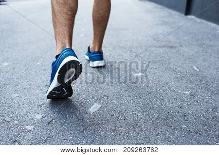 Cropped shot of sportsman in jogging sneakers running outside