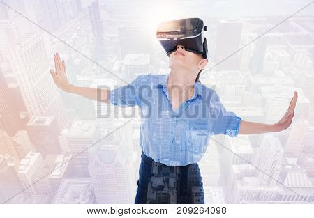 Engulfed in VR. Beautiful young woman wearing a VR headset and looking up while spreading hands wide as if leaning on the walls