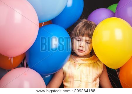 Sad Blond Little Girl With Colorful Balloons