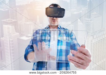 Fruitful technology interaction. Handsome bristled man tapping on the transparent tablet while wearing a VR headset and standing against an urban background