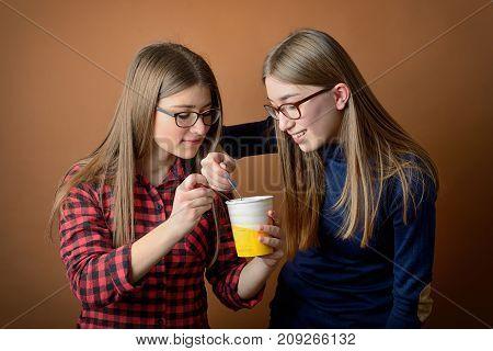 Young girls best friends sharing an ice-cream box