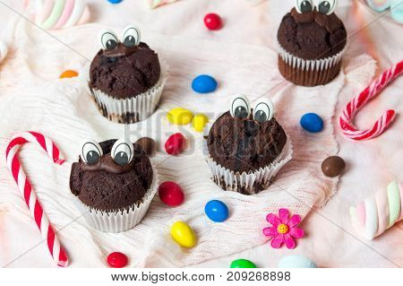 Chocolate Muffins With Edible Eyes And Colorful Bonbons