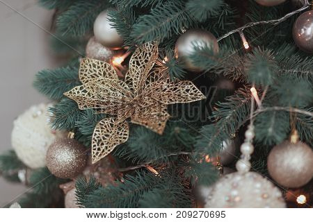 Flower Christmas tree Decoration, Gold Glossy Ornament Set, hanging on fir with balls and garland.