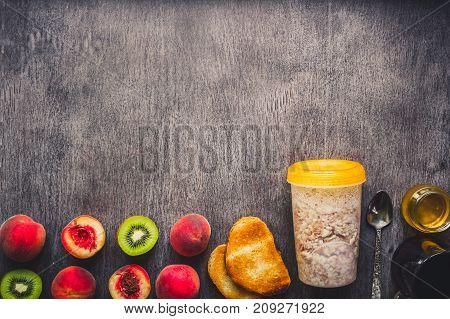 Ingredients for oatmeal on dark wooden table. Concept of healthy food. Top view, copy space. Flat lay. Still life. Toned