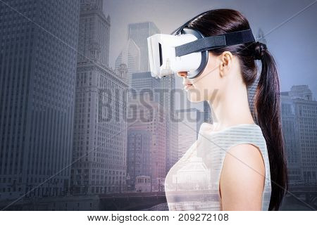 New-fangled device. The side view of a gorgeous dark-haired woman using VR headset while posing against an urban background