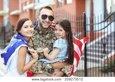 US army soldier with family and USA flag on street