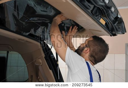 Worker tinting car window in shop