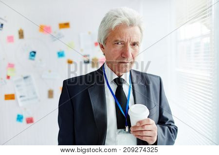 Experienced grey-haired investigator with glass of drink looking at camera