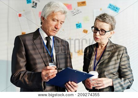 Two mature investigators reading important document with evidences of the crime