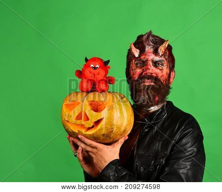 Man Wearing Scary Makeup Holds Pumpkin And Red Devil Toy