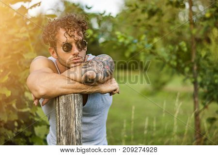 Portrait of handsome tattooed man in sunglasses leaning on pole looking away on natural background.