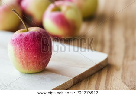 Stack of fuji apple and on cutting board put on wood table for background or wallpaper. Delicious sweet and juicy fuji apple for salad cooking or bakery. Fuji apple has origins in Japan. Goodness apple for fresh fruit concept.