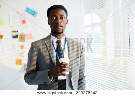 Confident young policeman in formalwear looking at camera on background of whiteboard with evidence