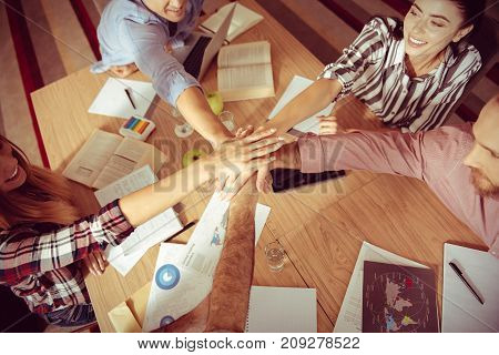 Team spirit. Close up of hands of young joyful nice people being held together while working in team