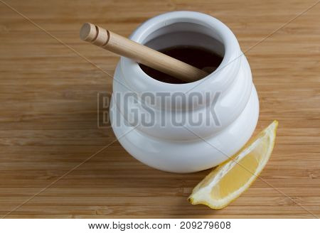 Brazilian lemon honey in a white ceramic honey pot, with wooden stirrer in the honey and a slice of lemon on the side, sitting on a bamboo tray, shot from a high angle.