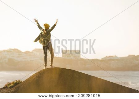 Happy woman with arms raised over the cliff seeing the beach