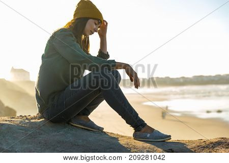 Beautiful woman sitting on a cliff over the beach