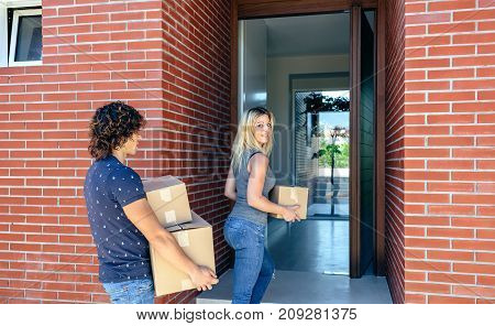 Moving couple carrying boxes to their new home