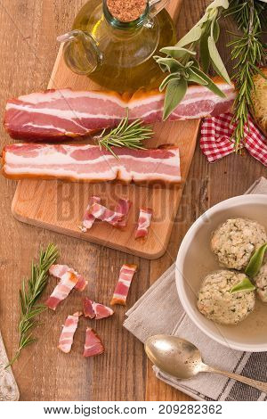 Canederli pasta with bacon on cutting board.